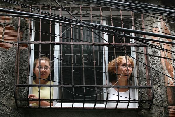 Residents peer from their window through a myriad of telephone wires in Parque da Cidade slum in Rio de Janeiro, Brazil, Oct. 27, 2005.(Australfoto/Douglas Engle)
