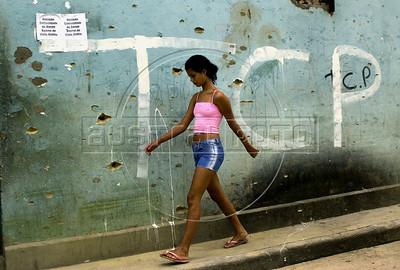 A girl walks alongside a wall perforated by bullets in Dende slum,  Rio de Janeiro, Brazil, August 31, 2004. (Renzo Gostoli/Austral Foto)