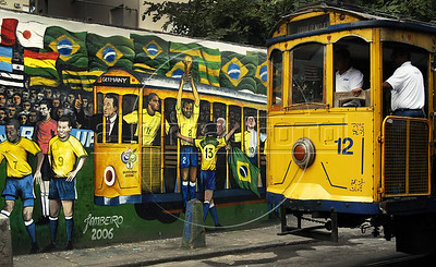 "A tipical tramway (bonde) past by a mural regarding the 2006 Germany Soccer World Cup in a street of Santa Tereza city district, Rio de Janeiro, Brazil, June 6, 2006. The "" bondinho"" of Santa Teresa is a historic tram line in Rio de Janeiro connecting the city centre with the primarily residential, inner-city neighbourhood of Santa Teresa, in the hills immediately southwest of downtown. In late August 2011 five people were killed and at least 27 injured when a tram derailed. All service has been indefinitely suspended since the accident. (Austral Foto/Renzo Gostoli)"