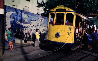"A tipical tramway (bonde) past by a mural regarding the 1986 Soccer World Cup in a street of Santa Tereza city district, Rio de Janeiro, Brazil, May 11, 1988. The "" bondinho"" of Santa Teresa is a historic tram line in Rio de Janeiro connecting the city centre with the primarily residential, inner-city neighbourhood of Santa Teresa, in the hills immediately southwest of downtown. In late August 2011 five people were killed and at least 27 injured when a tram derailed. All service has been indefinitely suspended since the accident. (Austral Foto/Renzo Gostoli)"