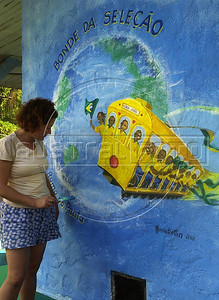 "A woman paints a mural regarding the 2002  Soccer World Cup in a street of Santa Tereza city district, Rio de Janeiro, Brazil, June 11, 2002. The "" bondinho"" of Santa Teresa is a historic tram line in Rio de Janeiro connecting the city centre with the primarily residential, inner-city neighbourhood of Santa Teresa, in the hills immediately southwest of downtown. In late August 2011 five people were killed and at least 27 injured when a tram derailed. All service has been indefinitely suspended since the accident. (Austral Foto/Renzo Gostoli)"