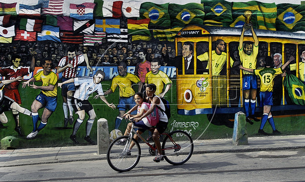 """Young people past by a mural regarding the 2006 Germany Soccer World Cup in a street of Santa Tereza city district, Rio de Janeiro, Brazil, June 6, 2006. The """" bondinho"""" of Santa Teresa is a historic tram line in Rio de Janeiro connecting the city centre with the primarily residential, inner-city neighbourhood of Santa Teresa, in the hills immediately southwest of downtown. In late August 2011 five people were killed and at least 27 injured when a tram derailed. All service has been indefinitely suspended since the accident. (Austral Foto/Renzo Gostoli)"""
