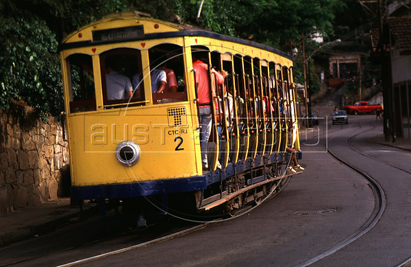 """A tipical tramway (bonde) runs alongside a street of Santa Tereza city district, Rio de Janeiro, Brazil, November 28, 1987. The """" bondinho"""" of Santa Teresa is a historic tram line in Rio de Janeiro connecting the city centre with the primarily residential, inner-city neighbourhood of Santa Teresa, in the hills immediately southwest of downtown. In late August 2011 five people were killed and at least 27 injured when a tram derailed. All service has been indefinitely suspended since the accident. (Austral Foto/Renzo Gostoli)"""