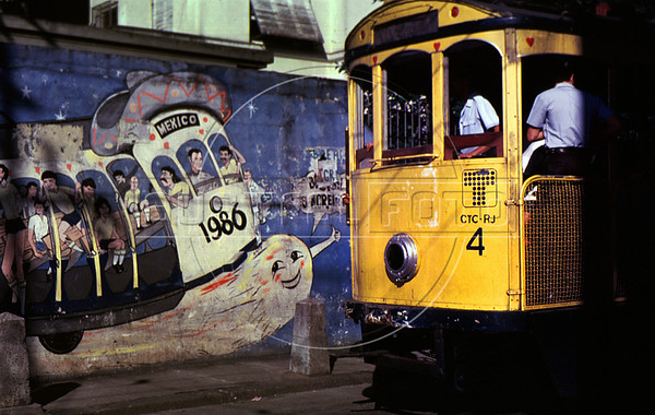 """A tipical tramway (bonde) past by a mural regarding the 1986 Soccer World Cup in a street of Santa Tereza city district, Rio de Janeiro, Brazil, May 11, 1988. The """" bondinho"""" of Santa Teresa is a historic tram line in Rio de Janeiro connecting the city centre with the primarily residential, inner-city neighbourhood of Santa Teresa, in the hills immediately southwest of downtown. In late August 2011 five people were killed and at least 27 injured when a tram derailed. All service has been indefinitely suspended since the accident. (Austral Foto/Renzo Gostoli)"""