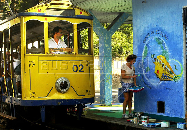 "A tipical tramway (bonde) past by a mural regarding the 2002  Soccer World Cup in a street of Santa Tereza city district, Rio de Janeiro, Brazil, June 11, 2002. The "" bondinho"" of Santa Teresa is a historic tram line in Rio de Janeiro connecting the city centre with the primarily residential, inner-city neighbourhood of Santa Teresa, in the hills immediately southwest of downtown. In late August 2011 five people were killed and at least 27 injured when a tram derailed. All service has been indefinitely suspended since the accident. (Austral Foto/Renzo Gostoli)"