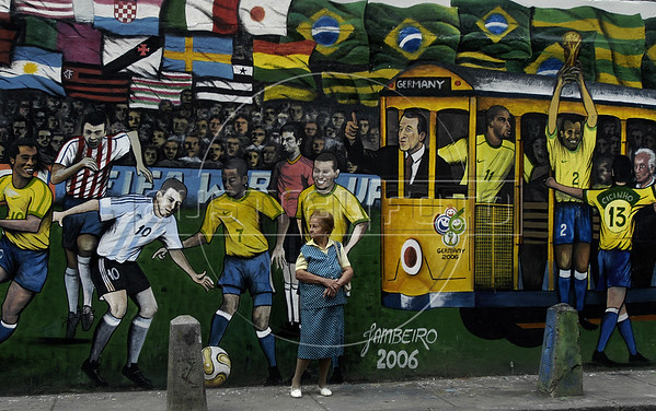 """A woman waits the tipical tramway (bonde) in front of a mural regarding the 2006 Germany Soccer World Cup in a street of Santa Tereza city district, Rio de Janeiro, Brazil, June 6, 2006. The """" bondinho"""" of Santa Teresa is a historic tram line in Rio de Janeiro connecting the city centre with the primarily residential, inner-city neighbourhood of Santa Teresa, in the hills immediately southwest of downtown. In late August 2011 five people were killed and at least 27 injured when a tram derailed. All service has been indefinitely suspended since the accident. (Austral Foto/Renzo Gostoli)"""