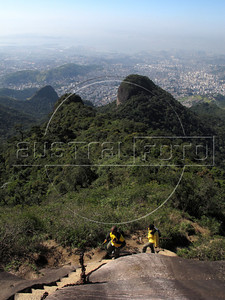 Hikers approach the top of the Tijuca Peak with of downtown Rio, top, in the background, from the Tijuca Forest National Park in Rio de Janeiro. The park, a forested mountain surrounded by an intensely populated urban area, is a model of preservation of the Brazil's Atlantic Forest ecosystem, of which only 7% remains. It is allegedly the largest urban forest in the world, and declared a National Park in 1961. Formerly a coffee planting area and Rio's water source, Brazilian Emperor Dom Pedro II had the area completely reforested in the 1860s as the city's water supply began to dwindle. It is home to hundreds of species of plants and wildlife, many threatened by extinction (Australfoto/Douglas Engle)
