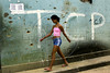 A girl walks alongside a wall perforated by bullets in Dende slum,  Rio de Janeiro, Brazil, August 31, 2004. (Renzo Gostoli/Austral Foto)