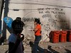 Pedestrians walk past grafitti provoking rival drug gangs in the Roquete Pinto favela, or slum, in Rio de Janeiro, Brazil, where Police Inspector Roberto Ubiratan Dias, 29, was killed by gang members as he was conducting an investigation. The assailants threw a grenade from the second story of a house at the inspector and police officers who accompanied him. A firefight followed in which the inspector and two assailants were killed. Shootouts between rival drug gangs and the police are common in Rio and the death toll rivals that of declared war zones.(AustralFoto/Douglas Engle)