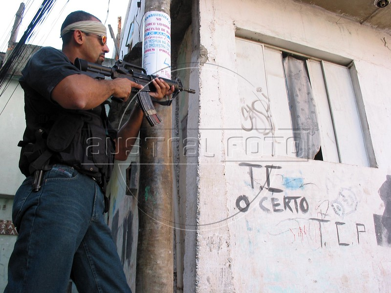 A police officer stands guard in the Roquete Pinto favela, or slum, in Rio de Janeiro, Brazil, where Police Inspector Roberto Ubiratan Dias, 29, was killed by gang members as he was conducting an investigation. The assailants threw a grenade from the second story of a house at the inspector and police officers who accompanied him. A firefight followed in which the inspector and two assailants were killed. Shootouts between rival drug gangs and the police are common in Rio and the death toll rivals that of declared war zones.(AustralFoto/Douglas Engle)