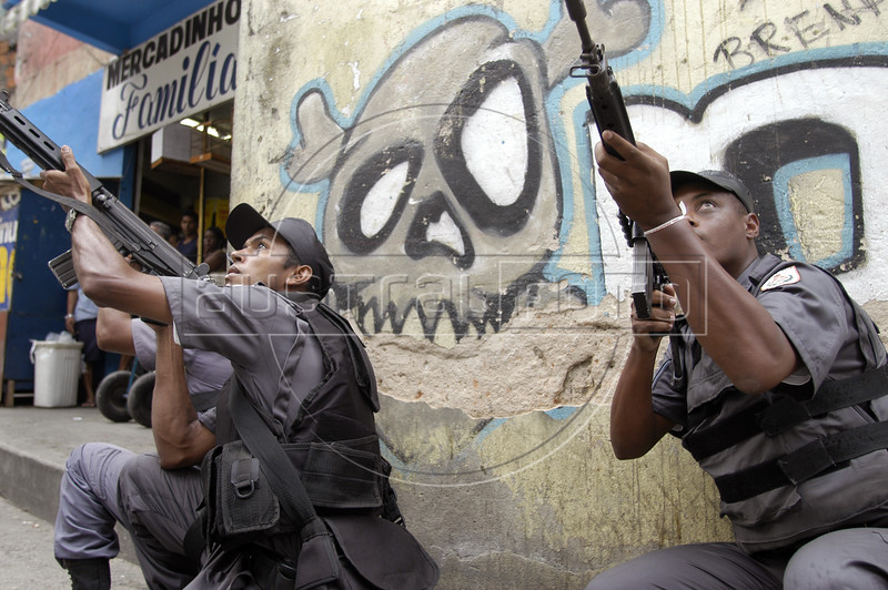 """Police stand guard near grafitti reading """"no war"""" in the Rocinha slum in Rio de Janeiro, Brazil, Monday, April 12, 2004. According to reports, about 1000 police officers invaded the slum after a battle between rival drug traffickers erupted during the weekend. At least eight people died during the confrontations.(Douglas Engle/Australfoto)"""
