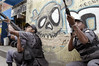 "Police stand guard near grafitti reading ""no war"" in the Rocinha slum in Rio de Janeiro, Brazil, Monday, April 12, 2004. According to reports, about 1000 police officers invaded the slum after a battle between rival drug traffickers erupted during the weekend. At least eight people died during the confrontations.(Douglas Engle/Australfoto)"