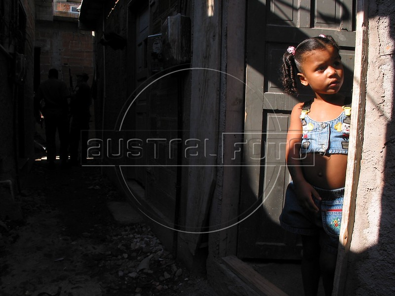 A girl peers out of her home in the Roquete Pinto favela, or slum, in Rio de Janeiro, Brazil, where Police Inspector Roberto Ubiratan Dias, 29, was killed by gang members as he was conducting an investigation. The assailants threw a grenade from the second story of a house at the inspector and police officers who accompanied him. A firefight followed in which the inspector and two assailants were killed. Shootouts between rival drug gangs and the police are common in Rio and the death toll rivals that of declared war zones.(AustralFoto/Douglas Engle)