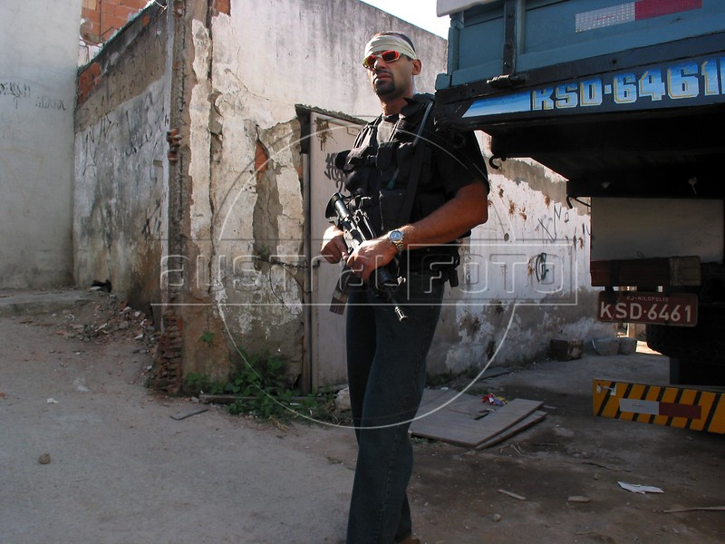 A heavily aremed police officer awaits his colleagues before entering the Roquete Pinto favela, or slum, in Rio de Janeiro, Brazil, where Police Inspector Roberto Ubiratan Dias, 29, was killed by gang members as he was conducting an investigation. The assailants threw a grenade from the second story of a house at the inspector and police officers who accompanied him. A firefight followed in which the inspector and two assailants were killed. Shootouts between rival drug gangs and the police are common in Rio and the death toll rivals that of declared war zones.	(AustralFoto/Douglas Engle)