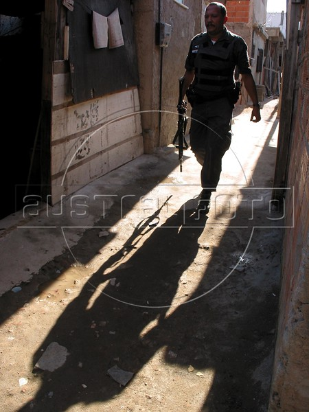 A police officer walk though an alley of the Roquete Pinto favela, or slum, in Rio de Janeiro, Brazil, where Police Inspector Roberto Ubiratan Dias, 29, was killed by gang members as he was conducting an investigation. The assailants threw a grenade from the second story of a house at the inspector and police officers who accompanied him. A firefight followed in which the inspector and two assailants were killed. Shootouts between rival drug gangs and the police are common in Rio and the death toll rivals that of declared war zones.	(AustralFoto/Douglas Engle)