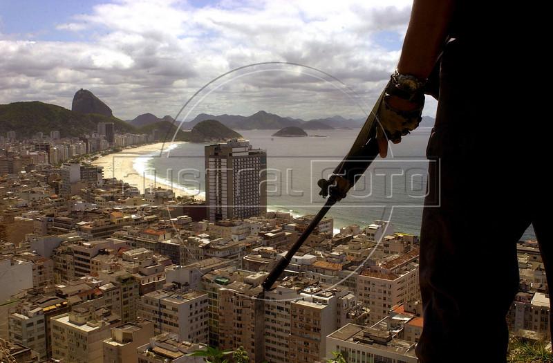 A Rio de Janeiro State military Police (PMERJ) officer look out over the famous Copacabana beach from a Rio de Janeiro favela or slum.(Douglas Engle/Australfoto)