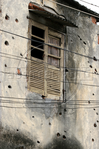 "A bullet-riddled house in the no-man's land area between two slums known as ""Vietnam"" in Rio de Janeiro, Brazil, Dec. 15, 2005. Police occupied the two slums after eight young people were kidnapped from one of them, allegedly by drug traffickers from a the other rival slum nearby. The kidnappings are the latest episode in a feud between the Vigario Geral and Parada de Lucas slums which has been going on for more that 20 years. The Vigario Geral slum was also site of an infamous massacre in 1993, in which police killed 21 people. Shootouts marked by indiscriminate shooting between rival drug gangs and the police are common in Rio and innocent bystanders have fallen victim to the deadly gunfire and the homicide rate of Rio rivals that of declared war zones.(AustralFoto/Douglas Engle)"