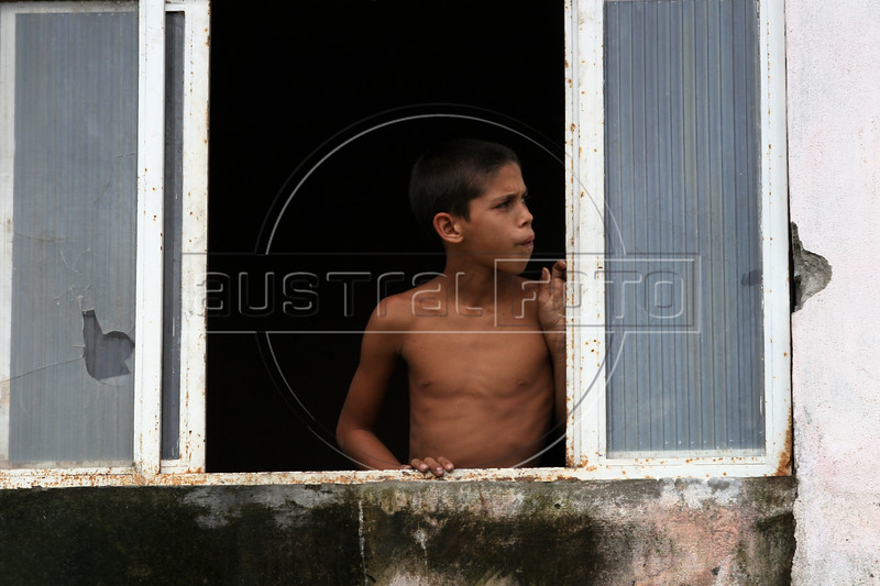 """A boy looks from a window damaged by bullets in the no-man's land area between two slums known as """"Vietnam"""" in Rio de Janeiro, Brazil, Dec. 15, 2005. Police occupied the two slums after eight young people were kidnapped from one of them, allegedly by drug traffickers from a the other rival slum nearby. The kidnappings are the latest episode in a feud between the Vigario Geral and Parada de Lucas slums which has been going on for more that 20 years. The Vigario Geral slum was also site of an infamous massacre in 1993, in which police killed 21 people. Shootouts marked by indiscriminate shooting between rival drug gangs and the police are common in Rio and innocent bystanders have fallen victim to the deadly gunfire and the homicide rate of Rio rivals that of declared war zones.(AustralFoto/Douglas Engle)"""