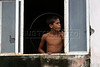 "A boy looks from a window damaged by bullets in the no-man's land area between two slums known as ""Vietnam"" in Rio de Janeiro, Brazil, Dec. 15, 2005. Police occupied the two slums after eight young people were kidnapped from one of them, allegedly by drug traffickers from a the other rival slum nearby. The kidnappings are the latest episode in a feud between the Vigario Geral and Parada de Lucas slums which has been going on for more that 20 years. The Vigario Geral slum was also site of an infamous massacre in 1993, in which police killed 21 people. Shootouts marked by indiscriminate shooting between rival drug gangs and the police are common in Rio and innocent bystanders have fallen victim to the deadly gunfire and the homicide rate of Rio rivals that of declared war zones.(AustralFoto/Douglas Engle)"