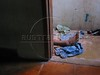 The foot of a shootout victim is seen through a doorway of a house in the Roquete Pinto favela, or slum, in Rio de Janeiro, Brazil, where Police Inspector Roberto Ubiratan Dias, 29, was killed by gang members as he was conducting an investigation. The assailants threw a grenade from the second story of a house at the inspector and police officers who accompanied him. A firefight followed in which the inspector and two assailants were killed. Shootouts between rival drug gangs and the police are common in Rio and the death toll rivals that of declared war zones.(AustralFoto/Douglas Engle)