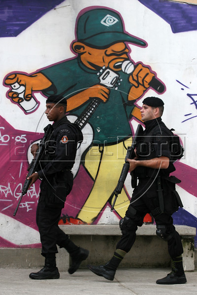 Members of the Rio de Janeiro State Police Special Operations Batallion (BOPE) walk past graffiti in the Vigario Geral favela, or slum, in Rio de Janeiro, Brazil, Dec. 15, 2005. Police occupied the slum after eight young people were kidnapped from there, allegedly by drug traffickers from a rival slum nearby. The kidnappings are the latest episode in a feud between the two slums run by drug traffickers from rival drug gangs, which has been going on for more that 20 years. The Vigario Geral slum was also site of an infamous massacre in 1993, in which police killed 20 people. Shootouts marked by indiscriminate shooting between rival drug gangs and the police are common in Rio and innocent bystanders have fallen victim to the deadly gunfire and the homicide rate of Rio rivals that of declared war zones.(AustralFoto/Douglas Engle)