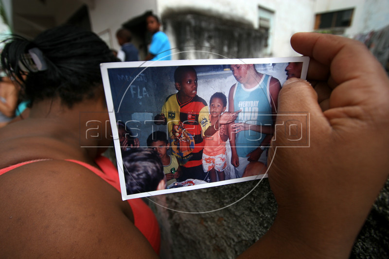 Denise Alves Tavares shows a photo of her son Douglas Roberto Alves, 16, wearing a red and black shirt in the Vigario Geral favela, or slum, in Rio de Janeiro, Brazil, Dec. 15, 2005. Police occupied the slum after eight young people were kidnapped, including Tavares' son, allegedly by drug traffickers from a rival slum nearby. The kidnappings are the latest episode in a feud between the two slums run by drug traffickers from rival drug gangs, which has been going on for more that 20 years. The Vigario Geral slum was also site of an infamous massacre in 1993, in which police killed 20 people. Shootouts marked by indiscriminate shooting between rival drug gangs and the police are common in Rio and innocent bystanders have fallen victim to the deadly gunfire and the homicide rate of Rio rivals that of declared war zones.(AustralFoto/Douglas Engle)