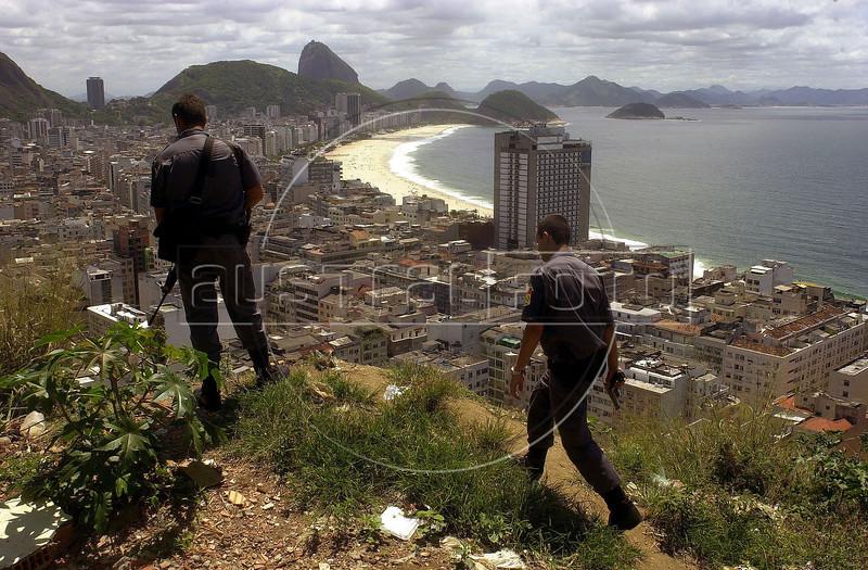 Rio de Janeiro State military Police (PMERJ) officers look out over the famous Copacabana beach from a Rio de Janeiro favela or slum.(Douglas Engle/Australfoto)