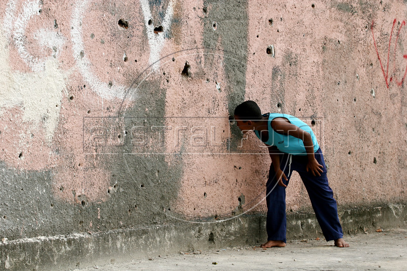 """A boy looks at a bullet-riddled wall in the no-man's land area between two slums known as """"Vietnam"""" in Rio de Janeiro, Brazil, Dec. 15, 2005. Police occupied the two slums after eight young people were kidnapped from one of them, allegedly by drug traffickers from a the other rival slum nearby. The kidnappings are the latest episode in a feud between the Vigario Geral and Parada de Lucas slums which has been going on for more that 20 years. The Vigario Geral slum was also site of an infamous massacre in 1993, in which police killed 21 people. Shootouts marked by indiscriminate shooting between rival drug gangs and the police are common in Rio and innocent bystanders have fallen victim to the deadly gunfire and the homicide rate of Rio rivals that of declared war zones.(AustralFoto/Douglas Engle)"""