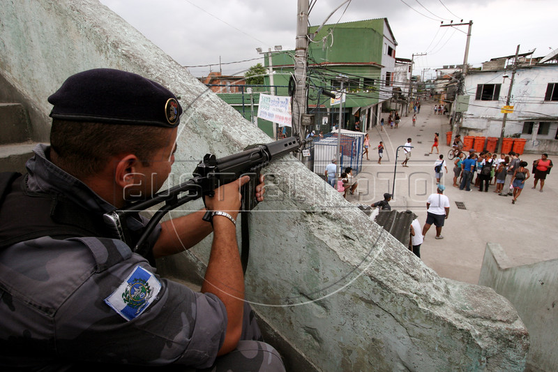 """A police officer """"protects"""" the Vigario Geral favela, or slum, in Rio de Janeiro, Brazil, Dec. 15, 2005. Police occupied the slum after eight young people were kidnapped from there, allegedly by drug traffickers from a rival slum nearby. The kidnappings are the latest episode in a feud between the two slums run by drug traffickers from rival drug gangs, which has been going on for more that 20 years. The Vigario Geral slum was also site of an infamous massacre in 1993, in which police killed 21 people. Shootouts marked by indiscriminate shooting between rival drug gangs and the police are common in Rio and innocent bystanders have fallen victim to the deadly gunfire and the homicide rate of Rio rivals that of declared war zones.(AustralFoto/Douglas Engle)"""