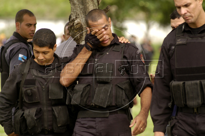"""Grieving colleagues attend the funeral of Rio's police special forces (BOPE) Sergeant Wilson Sant'anna, 28, killed the previous day with a single rifle shot to the abdomen in Rio de Janeiro. Life as one of Rio de Janeiro's 38,000 military police officers has never been an easy task, particularly for those whose mission it is to combat the city's three heavily armed drug factions, the Red Command, the Third Command and the Friends of the Friends or """"ADA"""". But a wave of police killings this year has underlined the growing dangers of law enforcement in this seaside tourist capital.(Australfoto/Douglas Engle)"""