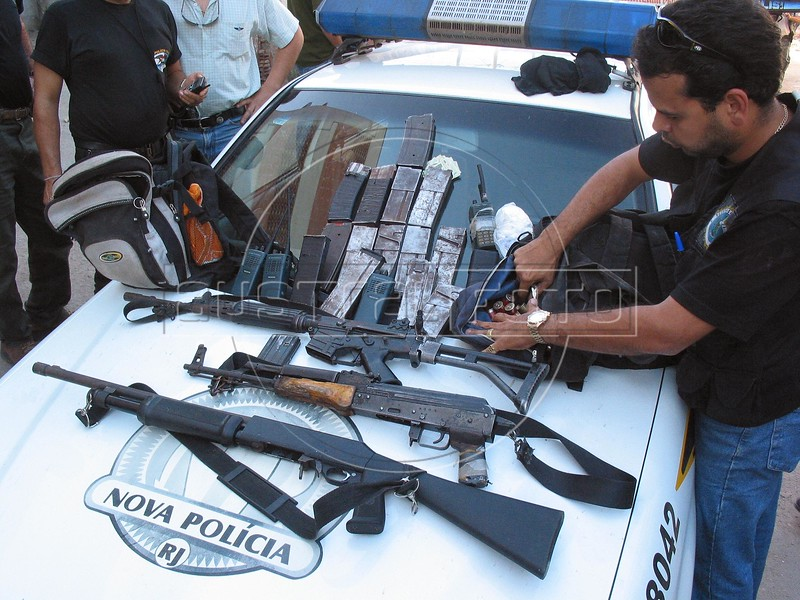Police display weapons found during a search of the Roquete Pinto favela, or slum, in Rio de Janeiro, Brazil, where Police Inspector Roberto Ubiratan Dias, 29, was killed by gang members as he was conducting an investigation. The assailants threw a grenade from the second story of a house at the inspector and police officers who accompanied him. A firefight followed in which the inspector and two assailants were killed. Shootouts between rival drug gangs and the police are common in Rio and the death toll rivals that of declared war zones.	(AustralFoto/Douglas Engle)