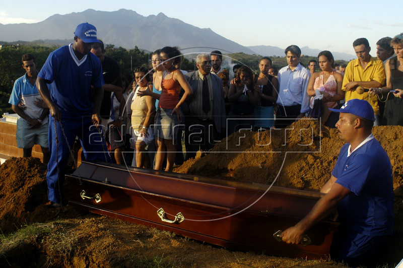 Cemetery workers bury the coffin of a massacre at one of several funerals at a cemetery in Nova Iguazu, Brazil, on Friday, April 1, 2005. In what was described as a 'massacre' and 'bloodbath', gunmen murdered at least 28 people in three separate killings in the outskirts of Rio de Janeiro, officials said Friday. The killings, which occurred late Thursday night in Nova Iguacu and Queimados, two poverty-ridden and crime-infested suburbs, 35 kilometers (22 miles)northwest of Rio de Janeiro, could have been the work of police officers.(AustralFoto/Douglas Engle)
