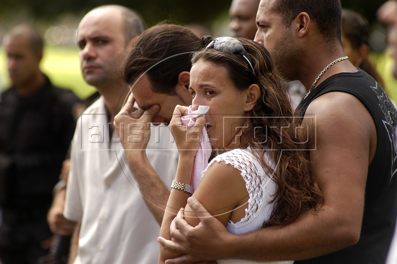 """Grieving friends and family attend the funeral of Rio's police special forces (BOPE) Sergeant Wilson Sant'anna, 28, killed the previous day with a single rifle shot to the abdomen in Rio de Janeiro. Life as one of Rio de Janeiro's 38,000 military police officers has never been an easy task, particularly for those whose mission it is to combat the city's three heavily armed drug factions, the Red Command, the Third Command and the Friends of the Friends or """"ADA"""". But a wave of police killings this year has underlined the growing dangers of law enforcement in this seaside tourist capital.(Australfoto/Douglas Engle)"""
