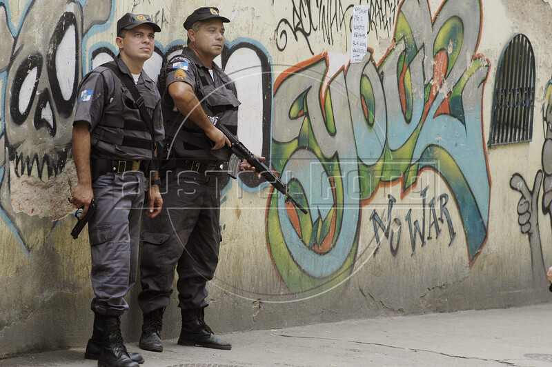 """Police stand guard near grafitti reading """"no war"""" in the Rocinha slum in Rio de Janeiro, Brazil, Monday, April 12, 2004. According to reports, about 1000 police officers invaded the slum after a battle between rival drug traffickers erupted diring the weekend. At least eight people died during the confrontations.(Douglas Engle/Australfoto)"""