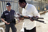 A workers carries guns to a deposit at a mobile gun collection station in Rio de Janeiro, Brazil, Nov. 19, 2004. Since the disarmament law, which limits firearms availability and use, took effect in December 2003, Brazil has one of the most modern firearm legislations in the world. But with 36,000 firearm deaths in 2003, the country also leads the world in firearm deaths . On average, 100 people are killed per day by firearms in Brazil. The number of homicides with firearms in Brazil is five times higher than the USA. (AustralFoto/Douglas Engle)