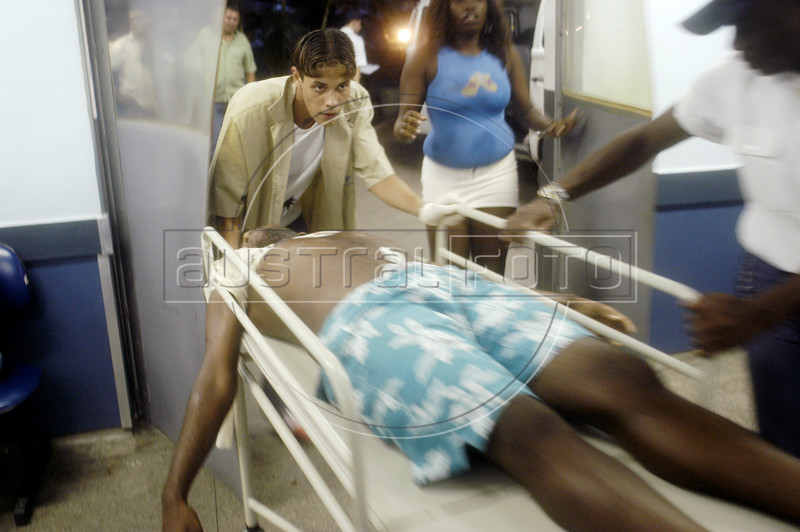 A gunshot victim is wheeled into the emergency room at the Bonsucesso Hospital in Rio de Janeiro, Jan 21, 2005. Shootouts marked by indiscriminate shooting between rival drug gangs and the police are common in Rio and innocent bystanders have fallen victim to the deadly gunfire. Situated in the working class north side of Rio, and close to two notorious slum complexes, the hospital personnel has earned a reputation as expert on gunshot wounds. The homicide rate of 8,408 in 1994 (about 23 per day) rivals that of declared war zones.(AustralFoto/Douglas Engle)