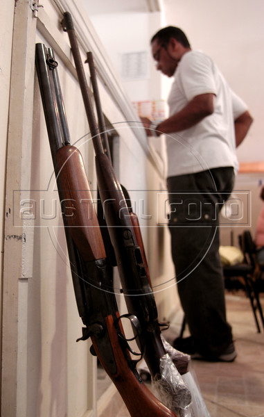 A worker catalogs guns at a gun collection station run by Viva Rio in Rio de Janeiro, Brazil, Nov. 11, 2004. Since the disarmament law, which limits firearms availability and use, took effect in December 2003, Brazil has one of the most modern firearm legislations in the world. But with 36,000 firearm deaths in 2003, the country also leads the world in firearm deaths . On average, 100 people are killed per day by firearms in Brazil. The number of homicides with firearms in Brazil is five times higher than the USA. (AustralFoto/Douglas Engle)