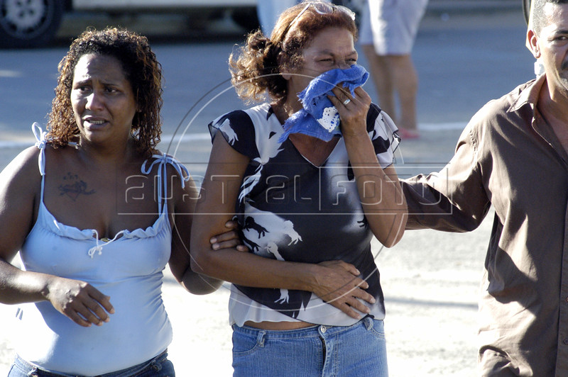 Friends and family of massacre victims weep before several funerals at a cemetery in Nova Iguazu, Brazil, on Friday, April 1, 2005. In what was described as a 'massacre' and 'bloodbath', gunmen murdered at least 28 people in three separate killings in the outskirts of Rio de Janeiro, officials said Friday. The killings, which occurred late Thursday night in Nova Iguacu and Queimados, two poverty-ridden and crime-infested suburbs, 35 kilometers (22 miles)northwest of Rio de Janeiro, could have been the work of police officers.(AustralFoto/Douglas Engle)