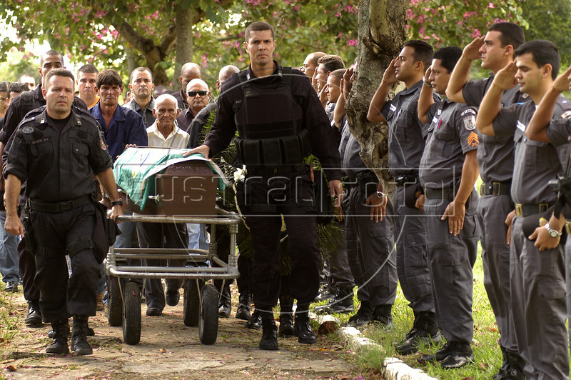 """Grieving colleagues, friends and family attend the funeral of Rio's police special forces (BOPE) Sergeant Wilson Sant'anna, 28, killed the previous day with a single rifle shot to the abdomen in Rio de Janeiro. Life as one of Rio de Janeiro's 38,000 military police officers has never been an easy task, particularly for those whose mission it is to combat the city's three heavily armed drug factions, the Red Command, the Third Command and the Friends of the Friends or """"ADA"""". But a wave of police killings this year has underlined the growing dangers of law enforcement in this seaside tourist capital.(Australfoto/Douglas Engle)"""