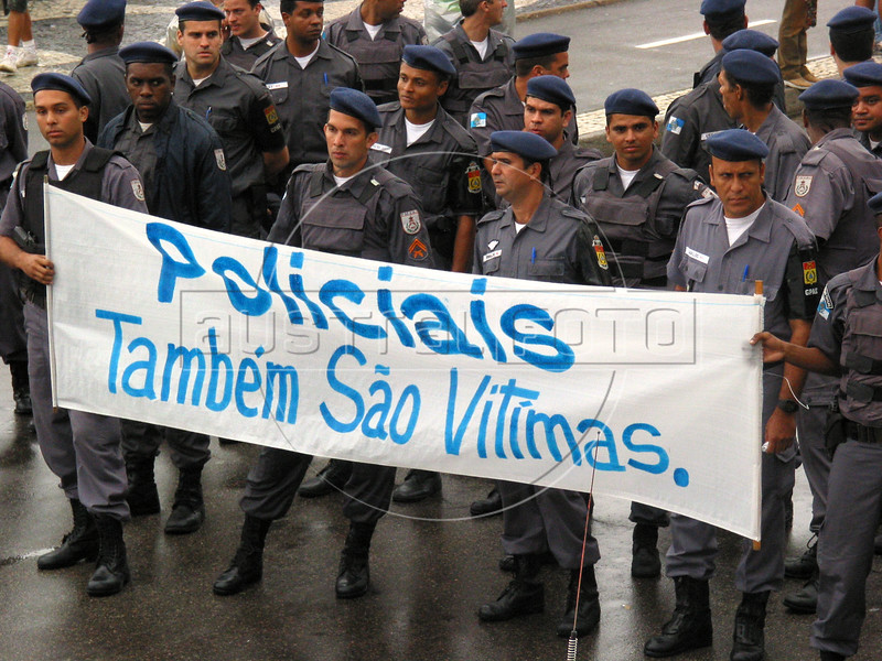 "Police officers carry a banner reading ""police are also victims"" during the ""March for a Gun Free Brazil"" on Copacabana beach in Rio de Janeiro, to pressure the Brazilian Congress regarding sweeping reforms to the countryÕs gun legislation. With over 40,000 gun deaths last year alone, the country has one of the highest gun death rates in the world, according to the UN. Few residents of large cities in Brazil can say that they themselves or someone they know has not been touched by armed violence. The Disarmament Statute would make it illegal to carry firearms, as well impose a series of restrictions for those who wish to purchase them.Ê The Statute also establishes October 2005 as the date for a national referedum to decide whether gun sales shouls be banned outright for civilians.(Douglas Engle/Australfoto)"
