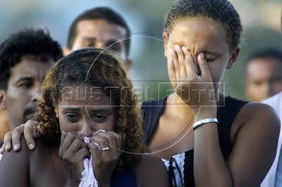 Friends and family of massacre victim Douglas Brasil da Paula, weep during his funeral at a cemetery in Nova Iguazu, Brazil, on Friday, April 1, 2005. In what was described as a 'massacre' and 'bloodbath', gunmen murdered at least 28 people in three separate killings in the outskirts of Rio de Janeiro, officials said Friday. The killings, which occurred late Thursday night in Nova Iguacu and Queimados, two poverty-ridden and crime-infested suburbs, 35 kilometers (22 miles)northwest of Rio de Janeiro, could have been the work of police officers,(AustralFoto/Douglas Engle)
