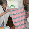 Rita Trainque in her kitchen shows her daughter Cindy Trainque one of the blankets she made for babies in Haiti. SENTINEL & ENTERPRISE/JOHN LOVE