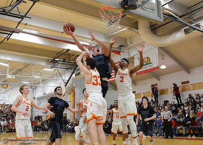 Pleasant Valley's Payton Williams (25) drives to the rim against Chico's Jackson Bragg (33) and Kaden Bradley (3) as the Chico High boys basketball team hosts Pleasant Valley in a cross-town rivalry Friday, Feb. 10,2017, in Chico, California. In the background, left to right, Brenden Bohannon (2), Kyle Lindquist (5), Ethan Hamel, Bishop Thomas (11) and Peyton Schneringer (14). (Dan Reidel -- Enterprise-Record)