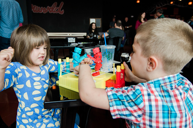 Elizaberth, 3, and Alan Fonatine, 5, play an intense game of Rock 'Em Sock 'Em Robots as River Styx Brewing in Fitchburg held their grand opening and ribbon cutting on Thursday, July 27, 2017. SENTINEL & ENTERPRISE / Ashley Green