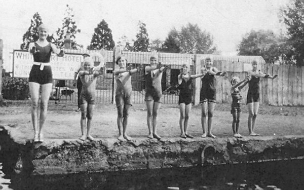 <font size=3><u> - Swimming Lesson - 1924 - </u></font> (BS0278)  From l. to r.: Mrs. Cumberlidge, Dawn (her daughter), Alma Thompson, Rene Bailey and Lizzie Bailey,  Alice Beale nee Lane, Tiger (daughter of  Mrs. Cumberlidge), Lizzie Parks nee Lane (DL's aunt).    Mr. Haynes is behind Dawn. He worked in the coal yard.  Mrs Cumberlidge was a Londoner who spent a few weeks each summer in Benson with her daughters and took it on herself to teach some of the local girls to swim. The girls are standing on what was known as the Camp Siding, which was 25 yards long, and the qualification to be able to swim when that length was completed.