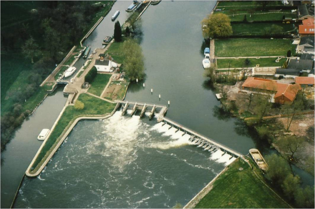 <font size=3><u> - Aerial view of lock and weir, 1985 - </u></font>(BS1323)  Air photo of Benson weir in Spring 1985.  Note the start of house building on the water meadow known as Winchmead