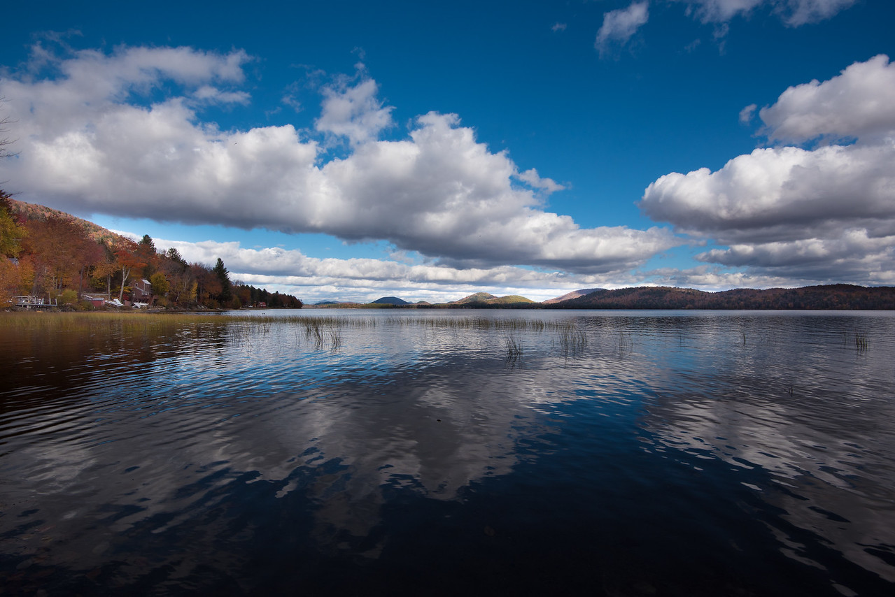 Piseco lake with bright blue sky and cumulus clouds