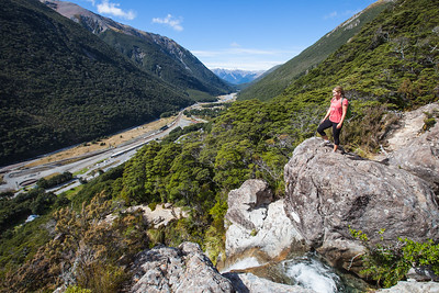 Female walker (20's) stands beside a waterfall and looks over Arthur's Pass village from the Avalanche Peak track