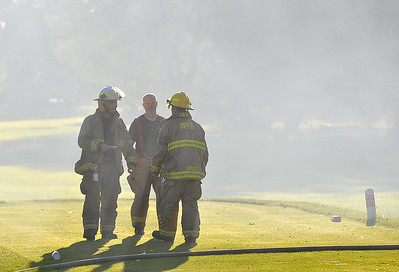 Lisa Yanick Litwiller - Morning Sun  Firefighters from Mt. Pleasant Fire Department —with help from Shepherd Tri-Township, Deerfield and Saginaw Chippewa Tribal Fire Departments— work to control a blaze in a storage barn on the west side of Riverwood Resort's golf course on Friday, July 28, 2017. A smokey haze filled the course and billowed across Broomfield Road as firefighters faced a bright setting sun as they worked Friday evening.