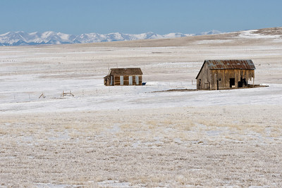 Old house and barn on top of Johnson's Mesa, New Mexico, with the Colorado Rockies in the distance.